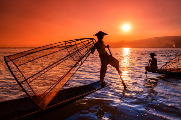 Fishermen on Inle Lake watching the sunset, Myanmar Fishermen on Inle Lake watching the sunset. Leg-rowing fishermen on Inle Lake are a major tourist destination in Myanmar (Burma). indochina stock pictures, royalty-free photos & images