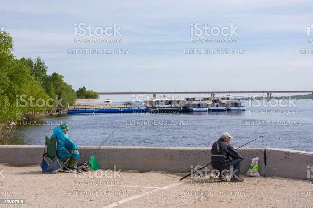Fishermen on the background of pleasure craft on the quay of the Central Embankment of G. Volgograd stock photo