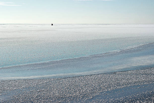 Fishermen on the iced sea. Winter sea. stock photo