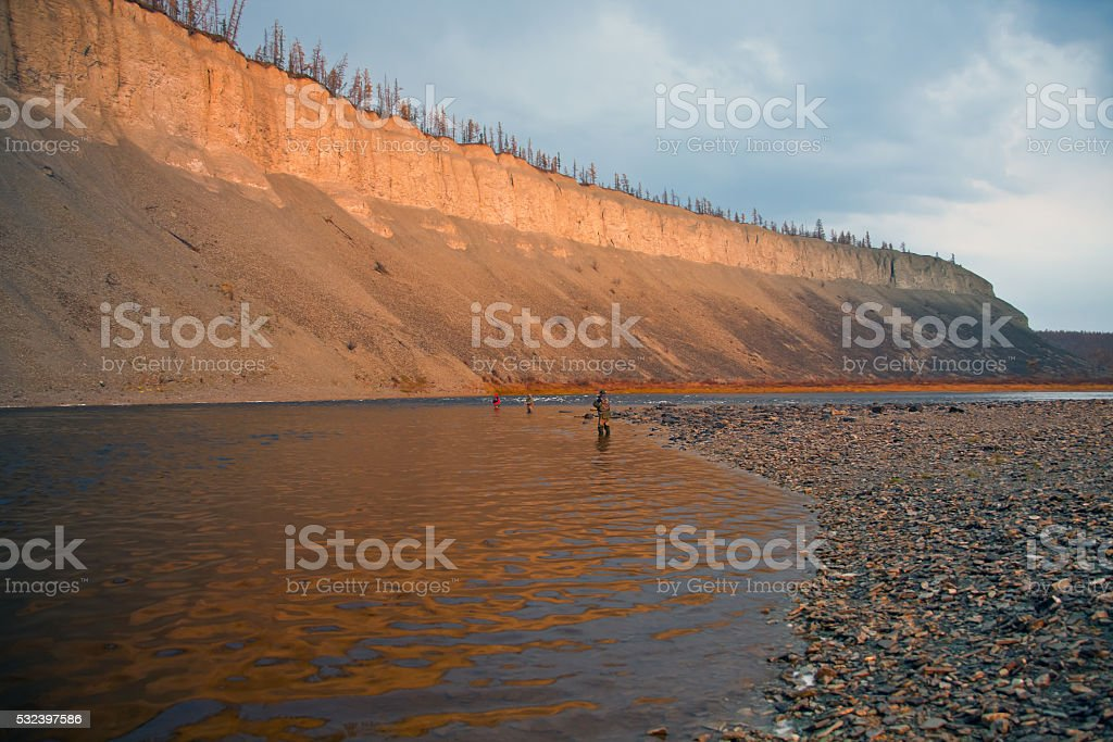 Fishermen on the Siberian taiga river in autumn in the North stock photo