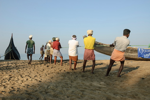Kovalam, India - February 22nd, 2010: Unidentified fishermen pull out a seine in Kovalam, Kerala, India. Fishing is still the main source of income for local people in Kerala.