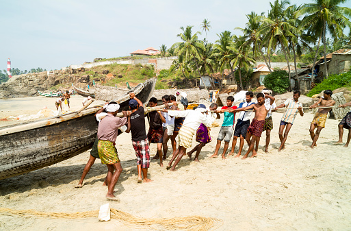 Kovalam, Kerala, India - January 15, 2012: Group of fishermen are pulling the fishing boat on the beach out of the Arabian Sea after fishing in Kovalam, Kerala, India.