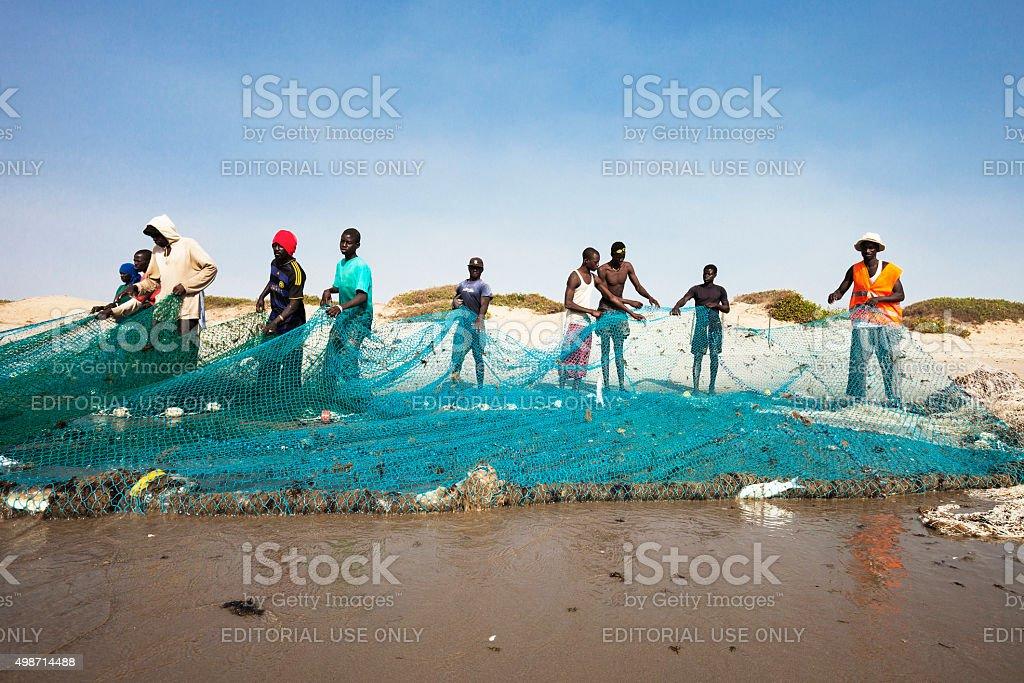 Fishermen pulling the net at the beach. stock photo