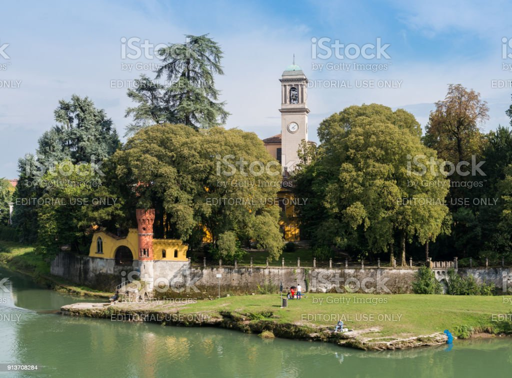 Fishermen relax next to a churchtower in Cassano d'Adda, Italy stock photo