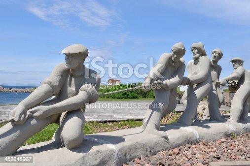 Magdalen Islands, Quebec, Canada - June 28, 2009: Beautiful sculpture of fishermen at Etang du Nord harbor . This work of art is created in 1990 by Roger Langevin to pay hommage to the fishermen in the island. It is about 15 meters long. It is now a local landmark.