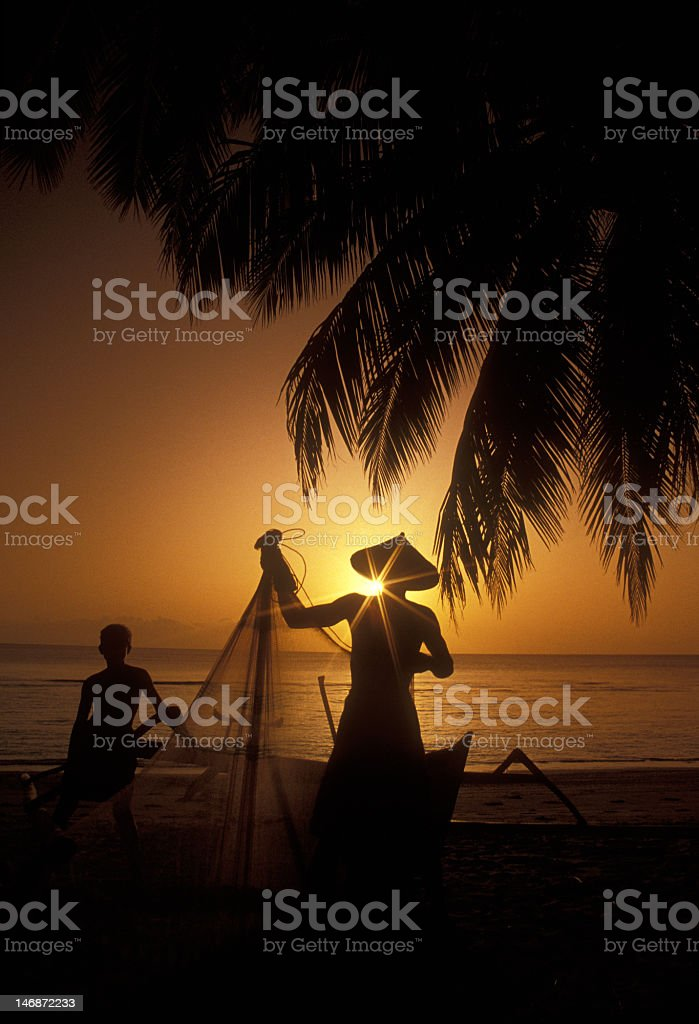 Fishermen Silhouettes, Indonesia, on Tropical Beach at Sunset stock photo