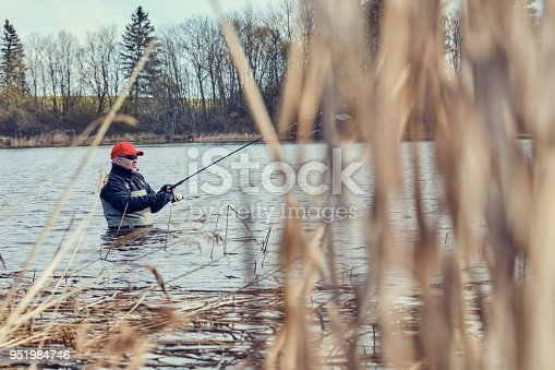 istock Fishermen spin fishing using chest waders to stay dry. 951984746