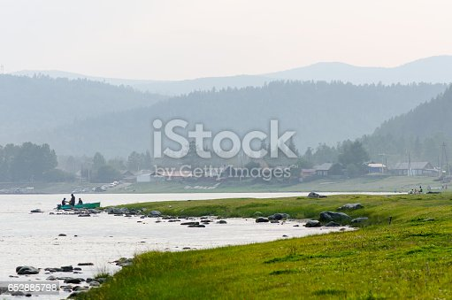istock fishermen standing in the water near board and old russian village 652885798