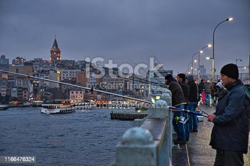 Istanbul, Turkey - December 31, 2013: Fishermen trying to catch fish on The Galata bridge in the evening in Istanbul, Turkey, during winter time with lighted ships and the Galata tower in the distance.