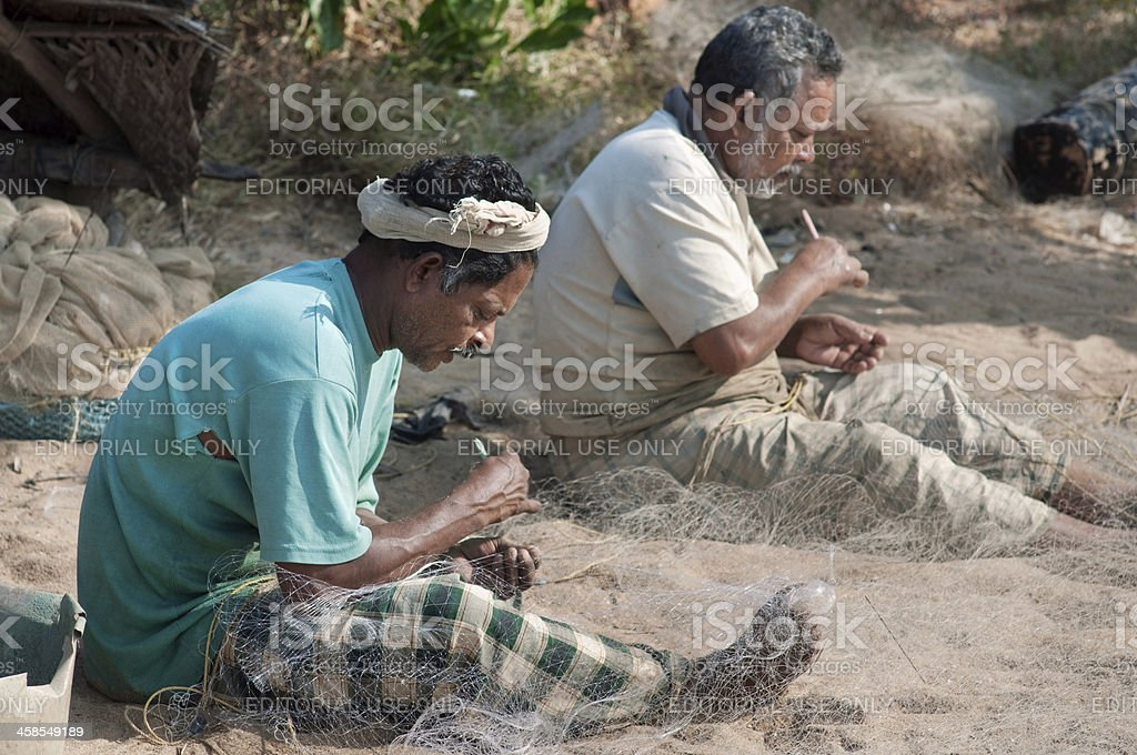 Fishermen working with nets on the beach stock photo