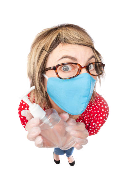 fisheye funny germophobic woman in face mask with hand sanitizer - sdominick stock pictures, royalty-free photos & images