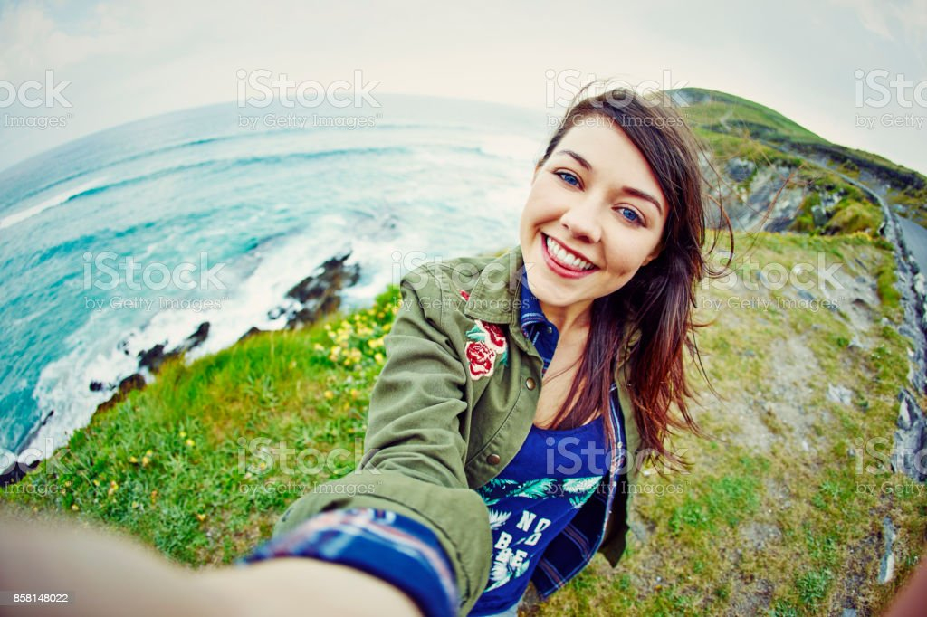 Fish-eye lens of happy woman taking selfie on mountain stock photo