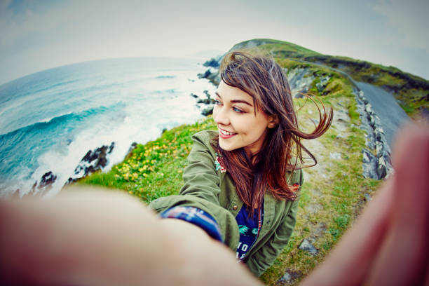 Fish-eye lens of woman taking selfie on mountain by sea Fish-eye lens of thoughtful woman taking selfie while sitting on mountain. Beautiful tourist with windswept brown hair is on grassy cliff by sea. She is wearing casuals during vacation. fish eye lens stock pictures, royalty-free photos & images