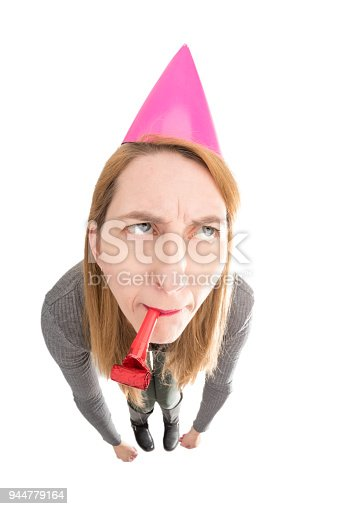 A fisheye of an unenthusiastic woman with a party hat and party blower.
