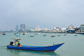 Fishing and tourist boat in the sea, at area Gulf of Thailand, Pattaya cityscape.
