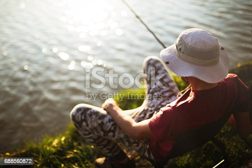 688562434istockphoto Fishing as recreation and sports displayed by fisherman at lake 688560872