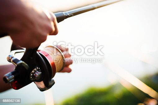 688562434istockphoto Fishing as recreation and sports displayed by fisherman at lake 688562136