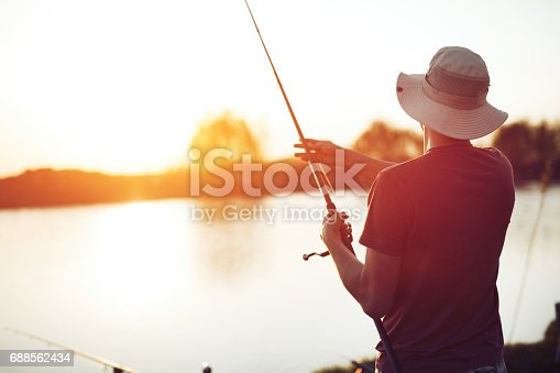 istock Fishing as recreation and sports displayed by fisherman at lake 688562434