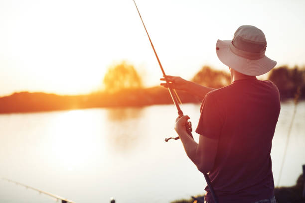 Fishing as recreation and sports displayed by fisherman at lake Fishing as recreation and sports displayed by fisherman at lake during sunset freshwater fishing stock pictures, royalty-free photos & images