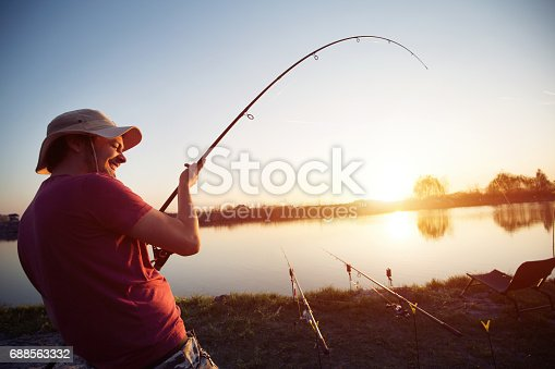 688562434istockphoto Fishing as recreation and sports displayed by fisherman at lake 688563332