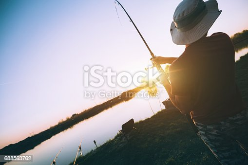 688562434istockphoto Fishing as recreation and sports displayed by fisherman at lake 688563762