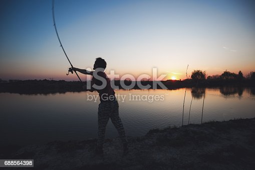 688562434istockphoto Fishing as recreation and sports displayed by fisherman at lake 688564398