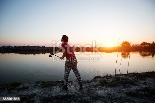 688562434istockphoto Fishing as recreation and sports displayed by fisherman at lake 688564558