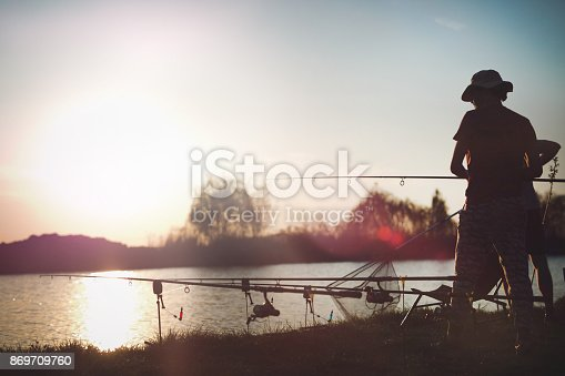 688562434istockphoto Fishing as recreation and sports displayed by fisherman at lake 869709760
