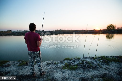 688562434istockphoto Fishing as recreation and sports displayed by fisherman at lake 869710472