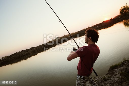 688562434istockphoto Fishing as recreation and sports displayed by fisherman at lake 869710610