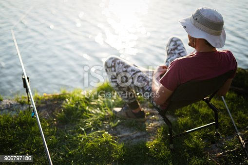 688562434istockphoto Fishing as recreation and sports displayed by fisherman at lake 906797186