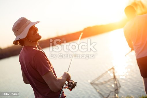 688562434istockphoto Fishing as recreation and sports displayed by fisherman at lake 906797460