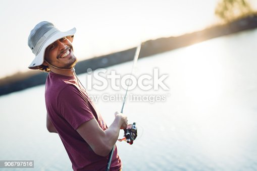 688562434istockphoto Fishing as recreation and sports displayed by fisherman at lake 906797516