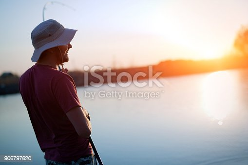 688562434istockphoto Fishing as recreation and sports displayed by fisherman at lake 906797620