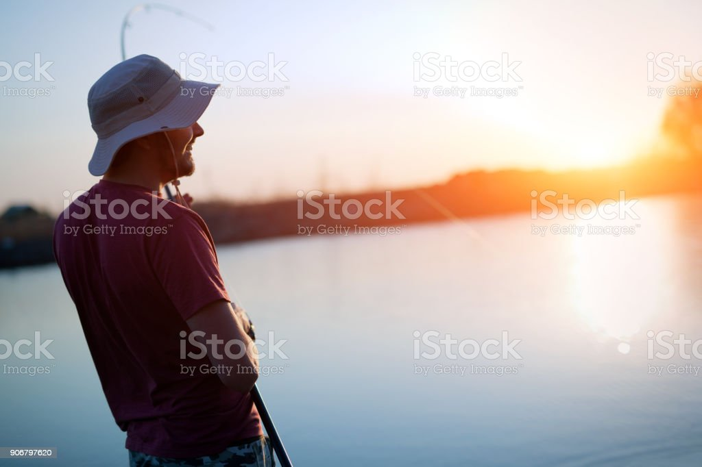 Fishing as recreation and sports displayed by fisherman at lake stock photo