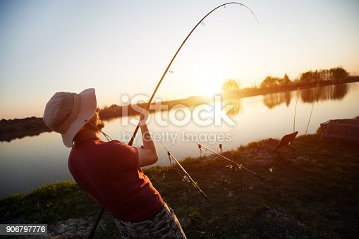 688562434istockphoto Fishing as recreation and sports displayed by fisherman at lake 906797776