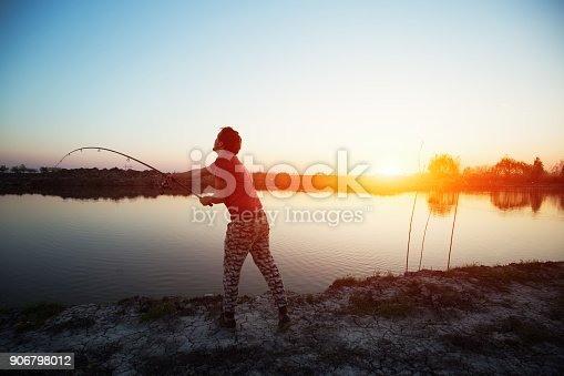 688562434istockphoto Fishing as recreation and sports displayed by fisherman at lake 906798012