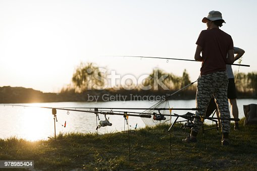 688562434istockphoto Fishing as recreation and sports displayed by fisherman at lake 978985404