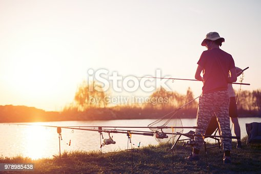 688562434istockphoto Fishing as recreation and sports displayed by fisherman at lake 978985438