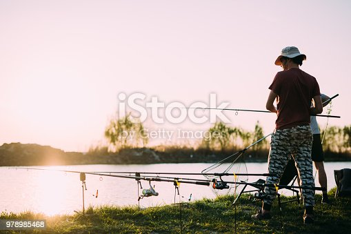 688562434istockphoto Fishing as recreation and sports displayed by fisherman at lake 978985468