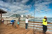 Daytona Beach, Florida - December 1, 2019:  People cast lines and fish off the pier along the shore of the Atlantic Ocean in Daytona Beach Florida USA