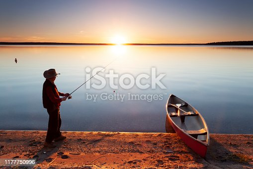 Man with cowboy hat fishing on a very beautiful, calm evening, with a sunset. Image taken from a tripod. Prince Albert National Park, Saskatchewan, Canada.