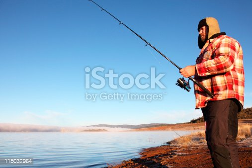 A male fishing for trout at Sunrise, Lake Eucumbene NSW Australia, on a cold but sunny morning