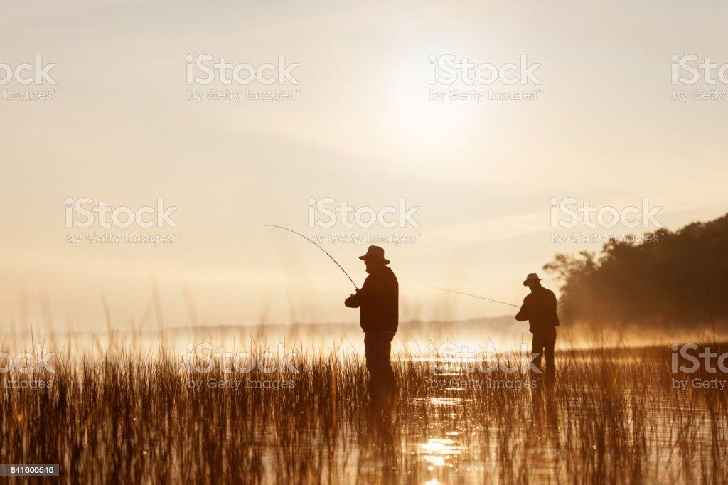 Fishing at sunrise stock photo