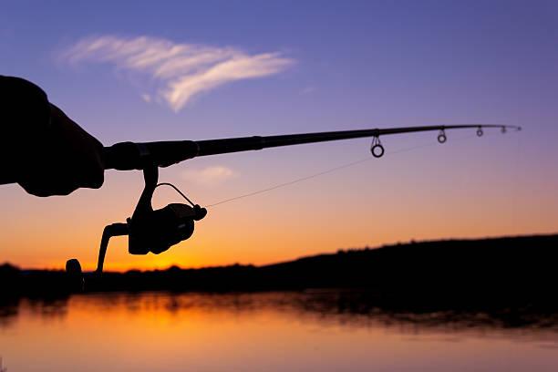fishing at sunset near the sea - 釣りをする ストックフォトと画像