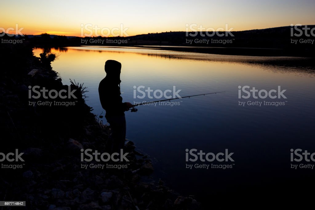 fishing at sunset near the sea. stock photo
