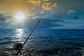 View from a catamaran boat sailing off the coast of Kauai, Hawaii. Fishing rod on foreground.