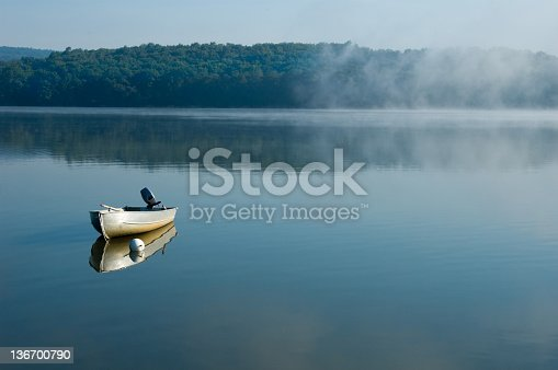 Fishing boat tied on a calm misty morning lake, alone and waiting, Pennsylvania, PA, USA.