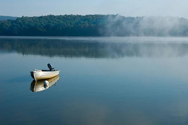 Fishing Boat Alone on Calm Morning Lake stock photo