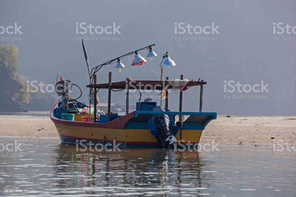 Fishing boat anchored near sandy shallow royalty-free stock photo